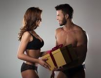 Mann, der der Frau Geschenk gibt Stockbild