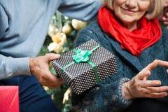 Mann, der der Frau Weihnachtsgeschenk am Speicher gibt Stockbilder