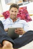 Mann, der in der Garten-Hängematte unter Verwendung Digital-Tablets sich entspannt Lizenzfreies Stockbild