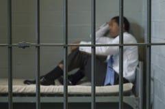 Mann, der in der Gefängnis-Zelle sitzt Lizenzfreie Stockfotografie