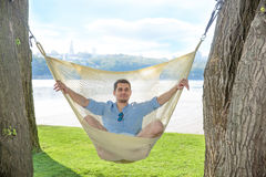 Mann, der in der Hängematte sich entspannt Lizenzfreie Stockfotografie