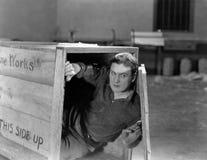 Mann, der in der hölzernen Kiste sich versteckt (alle dargestellten Personen sind nicht längeres lebendes und kein Zustand existi stockbild