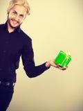 Mann, der in der Hand anwesende grüne Geschenkbox hält Stockbilder