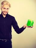 Mann, der in der Hand anwesende grüne Geschenkbox hält Stockfotos