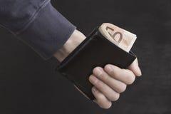 Mann, der in der Hand einen Geldbeutel mit Geld hält; Hippie Stockfoto