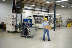 Mann, der in der industriellen Herstellungs-Fabrik arbeitet Stockfotos