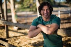Mann, der an der Kamera in der Ranch lächelt stockfotografie
