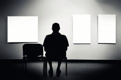 Mann, der in der Kunstgalerie sitzt Lizenzfreie Stockfotos