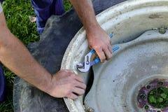Mann, der an der Reparatur des Traktorreifens arbeitet Lizenzfreie Stockfotos