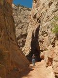 Mann, der in der schmalen Wüstenschlucht wandert Lizenzfreie Stockfotos