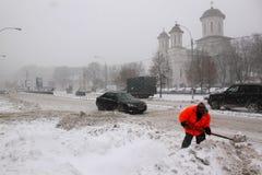 Mann, der an der Schneeräumung arbeitet Lizenzfreie Stockfotos