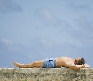 Mann, der in der Sonne liegt Lizenzfreies Stockfoto