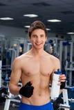 Mann, der in der Turnhalle nachdem dem Trainieren lächelt stockbild