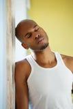 Mann, der an der Wand mit den Augen geschlossen sich lehnt Lizenzfreies Stockfoto