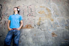 Mann, der an der Wand mit Graffiti sich lehnt Lizenzfreie Stockfotos