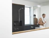 Mann, der an der Wanne im Badezimmer sich lehnt Lizenzfreies Stockfoto