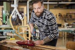 Mann, der an der Werkstatt mit Gitarre arbeitet Stockfotos