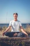 Mann, der in der Yogahaltung sitzt Stockfotos