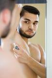 Mann, der desodorierendes Mittel anwendet Lizenzfreie Stockfotos