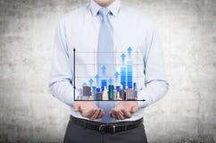 Mann, der Diagramm und Wolkenkratzer hält Lizenzfreies Stockfoto