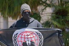 Mann, der die anonyme Flagge hält Stockfoto
