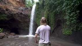 Mann, der die Arme victoriously erreichen Wasserfall anhebt stock footage