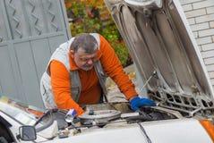 Mann, der die Automotorreparatur im Freien tut Stockbilder