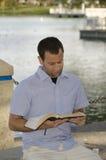 Mann, der die Bibel am See liest lizenzfreie stockfotos