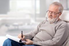 Mann, der die Einkaufsliste für Feiertage macht Lizenzfreies Stockfoto