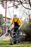 Mann, der die Fahrradkette instandh?lt w?hrend der neuen Jahreszeit schmiert lizenzfreie stockfotografie