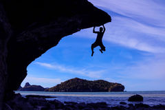 Mann, der die Felsen auf dem Strand klettert Lizenzfreies Stockbild