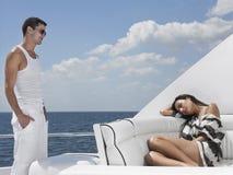 Mann, der die Frau schläft auf Sofa In Yacht betrachtet Stockfotografie