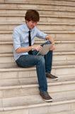 Mann, der die intelligente Tablette sitzt auf Treppen betrachtet lizenzfreie stockfotografie