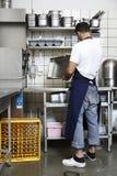 Mann, der die Küche säubert Stockbilder