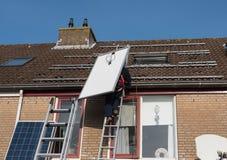 Mann, der die Leiter mit Sonnenkollektor klettert Lizenzfreie Stockfotos