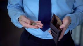 Mann, der die Münzen überlassen folgendes Gehalt, niedriges Einkommen, Geldmangel, Armut zählt lizenzfreies stockbild