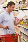 Mann, der die Nahrungsmittelkennzeichnung im Supermarkt überprüft Lizenzfreies Stockfoto