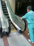 Mann, der die Rolltreppengefahren säubert Tokyo, Japan lizenzfreies stockbild