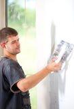 Mann, der die Wand vergipst stockbild