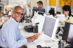 Mann, der Digital-Tablette im besetzten kreativen Büro verwendet Stockfotos