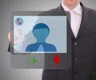Mann, der digitale Schnittstelle zu anschließendem Videoschwätzchen verwendet. Lizenzfreies Stockbild