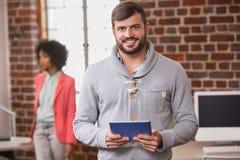 Mann, der digitale Tablette mit Kollegen hinten im Büro verwendet Lizenzfreie Stockfotografie