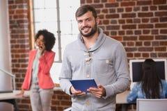Mann, der digitale Tablette mit Kollegen hinten im Büro verwendet Stockfoto