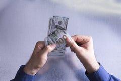 Mann, der 100 Dollarscheine zählt oder zahlt Stockfoto