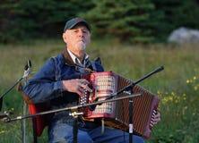 Mann, der draußen Acordian spielt Lizenzfreie Stockfotografie