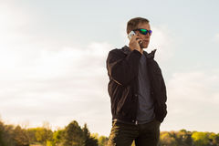 Mann, der draußen auf Smartphone spricht lizenzfreies stockfoto