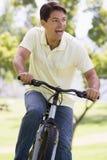 Mann, der draußen das Fahrradlächeln reitet Lizenzfreie Stockfotos