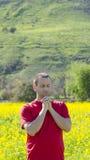 Mann, der draußen in der Natur allein betet Lizenzfreie Stockbilder