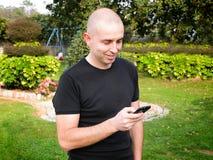 Mann, der draußen ein intelligentes Telefon verwendet Stockbild