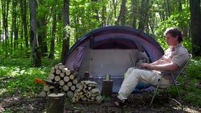 Mann, der draußen in einem Zeltlager arbeitet stock video footage